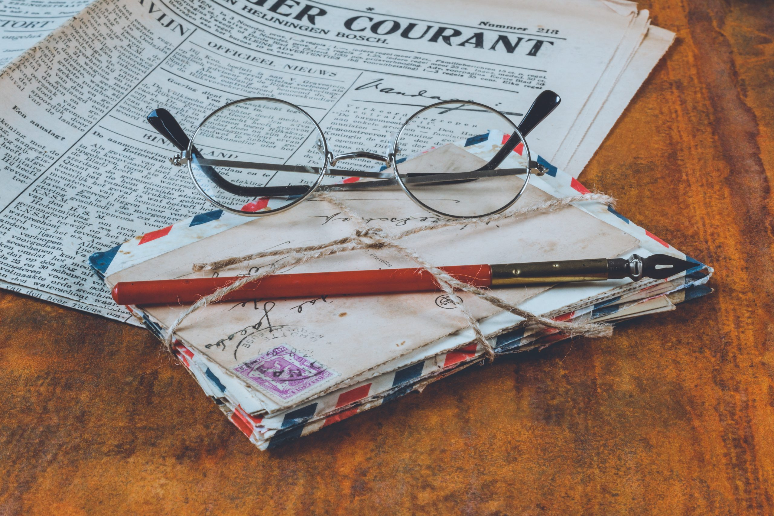 letters-and-an-eyeglass-on-table-1809342